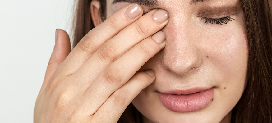 a woman touching her eyelid with her hand