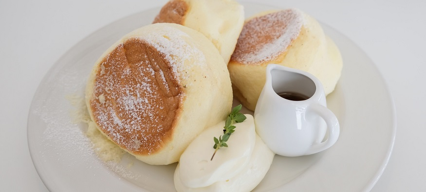fluffy japanese pancakes with a jug of maple syrup on the side