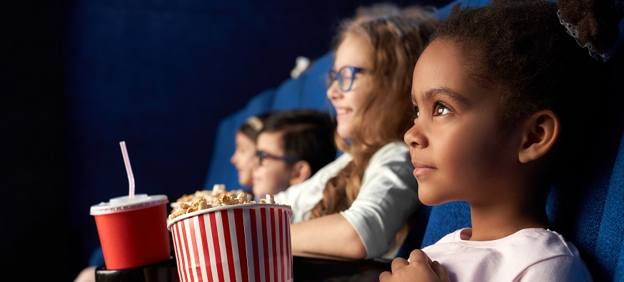a little girl eating popcorn and watching a film in a movie theatre