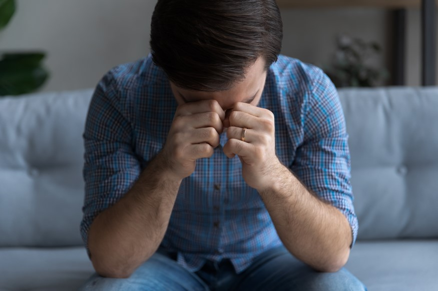 man sitting on couch suffering from stress depression and headaches