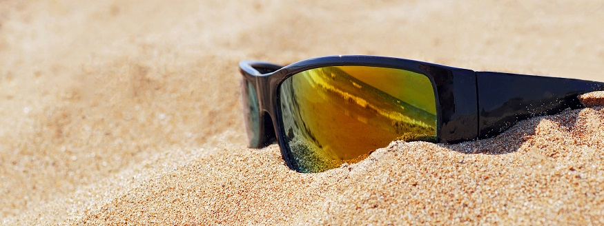 wrap around sunglasses on a beach in the sand