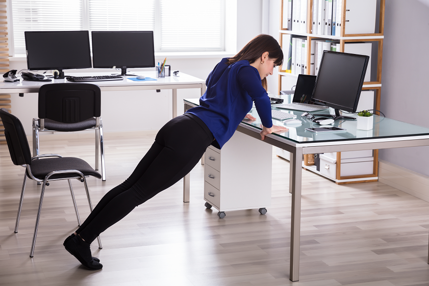 Woman doing a push up at her desk