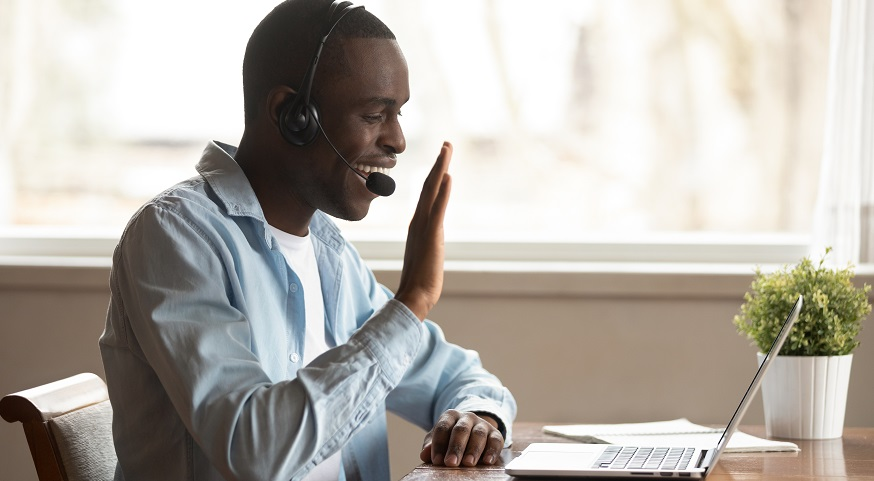 a male wearing a headset waving to his computer screen on a video chat