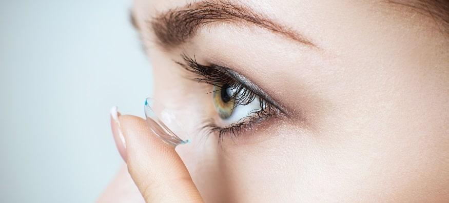 a woman applying contact lenses