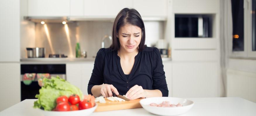 woman chopping onions crying